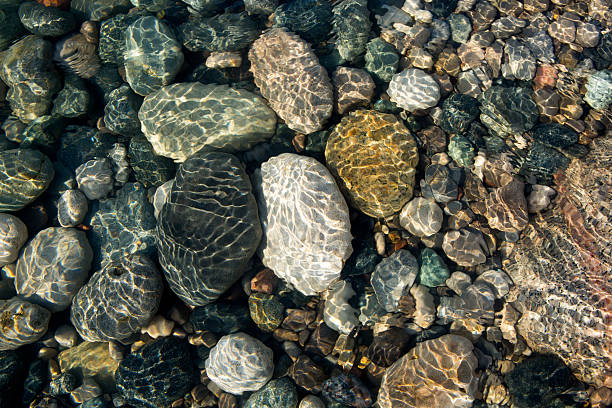 Stones in water Ripples on the water surface in shallow water with colourful stones. wading stock pictures, royalty-free photos & images