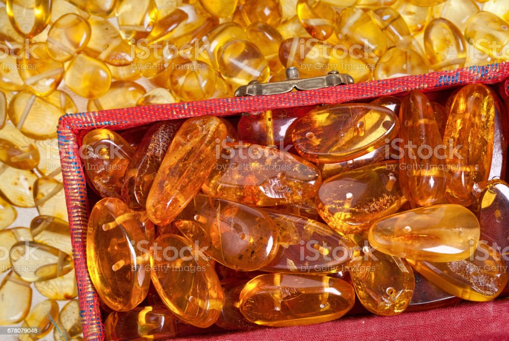 Stones of a dark yellow amber in an antique red box close-up. stock photo