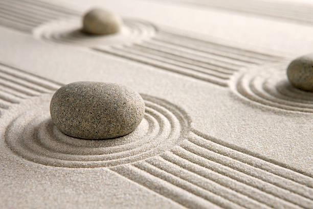 Stones on a neatly raked mini Zen garden stock photo