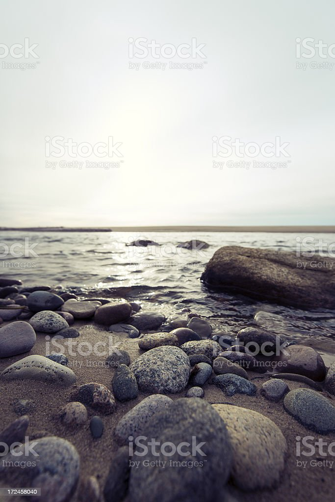 Stones on a remote beach with sunset in background (XXXLarge) royalty-free stock photo