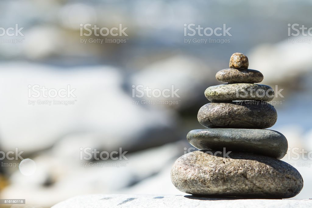 Stones pyramid on pebble beach symbolizing stability, zen, harmony, balance. stock photo