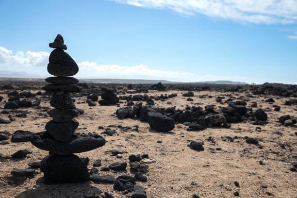 Stones pyramid on sand symbolizing zen, harmony, Stone balancing – zdjęcie