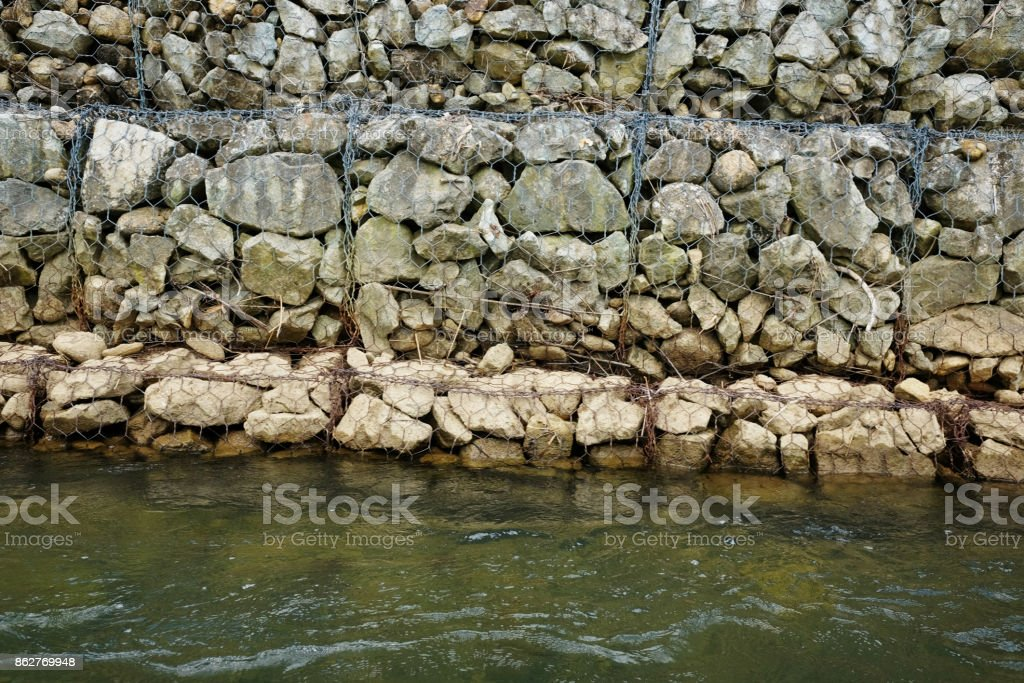 Stones wall in steel mesh cage for block Ground breaking on riverside stock photo