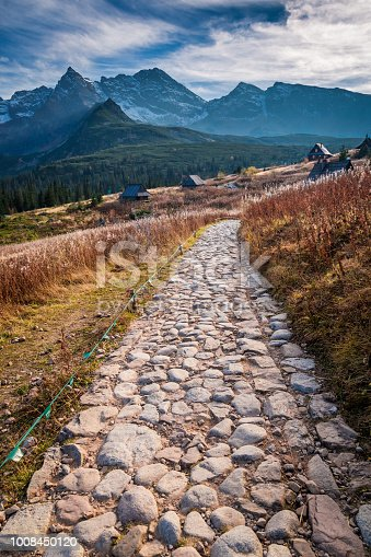 870409146 istock photo Stony path to the mountains valley at sunset in autumn 1008450120