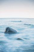 Stony sea shore sea, nice romantic evening background. Light blue