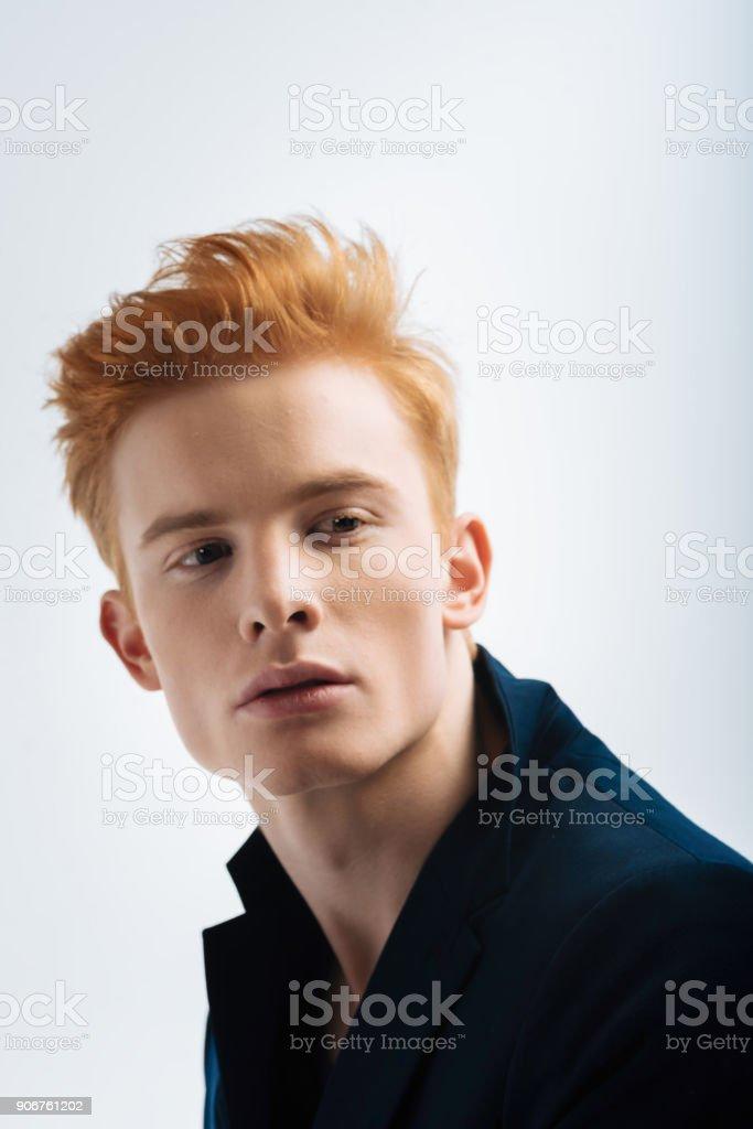 Stony-faced red-haired man looking in the distance stock photo