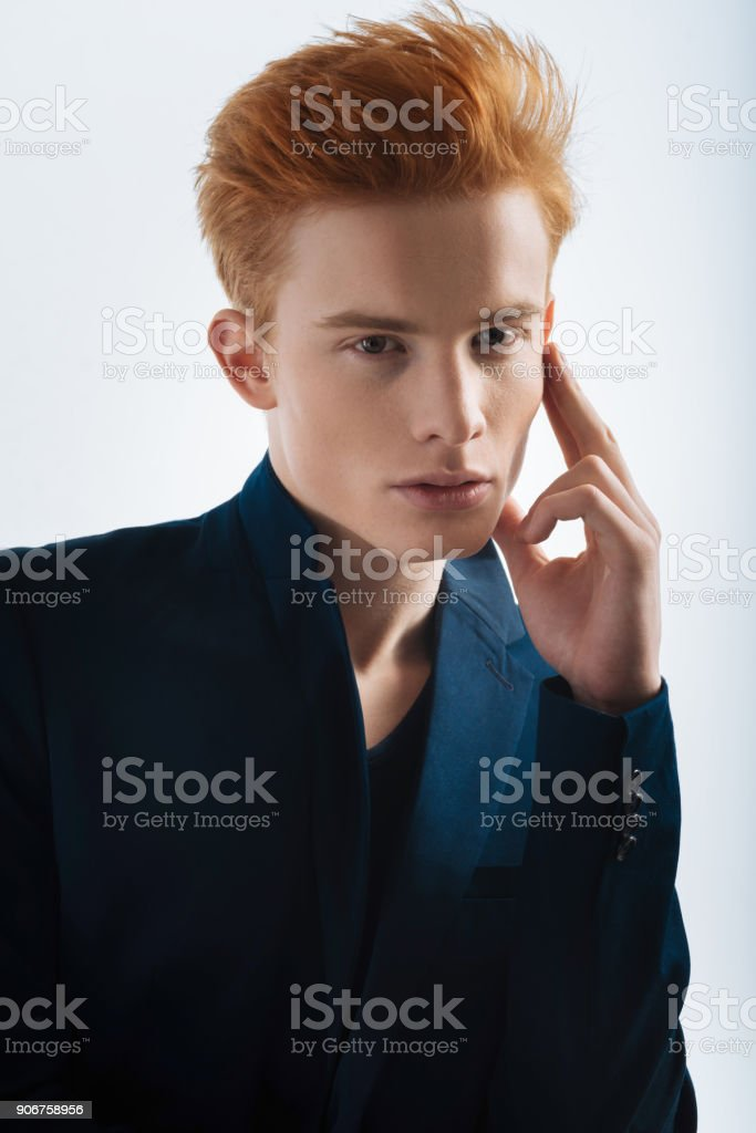 Stony-faced young man touching his forehead stock photo