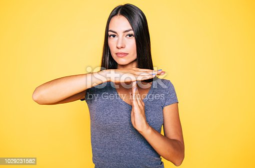 Stop and think. Portrait of young confident beautiful woman in casual wear is doing T symbol or sign with help of her hands and looks on camera