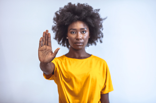 Photo of African american young woman making stop gesture with palm of her hand on grey background