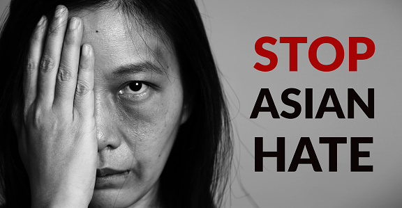 stop Asian hate campaign. Asia woman with bruise on arms and face, raise one hand and cover one face side. word stop Asian hate at copy space for poster of campaign.