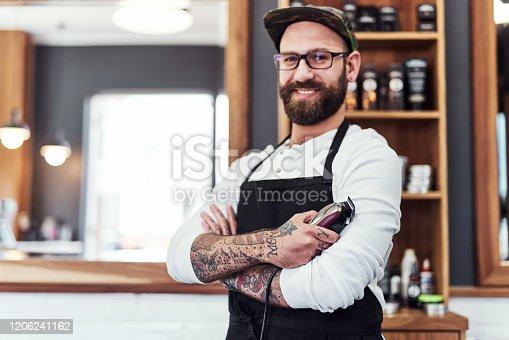 Portrait of a handsome young barber posing with his arms folded inside his barbershop