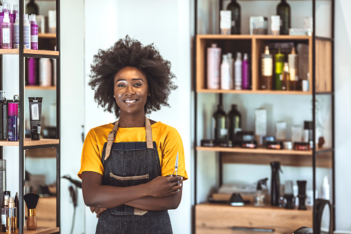 Smiling African American female barber standing with arms crossed in hair salon. Portrait of confident young woman is working at barber shop