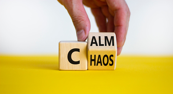 Stop chaos, time to calm. Male hand turns a wooden cube and changes the word 'chaos' to 'calm'. Beautiful yellow table, white background, copy space. Business and chaos or calm concept.