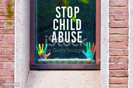 Stop child abuse written on the window of a building with mockup model child hands.