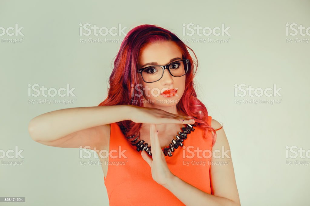 Stop. Closeup portrait, young, unhappy, serious woman showing time out hands gesture  isolated green wall background. Positive human emotion facial expressions feeling body language reaction attitude stock photo