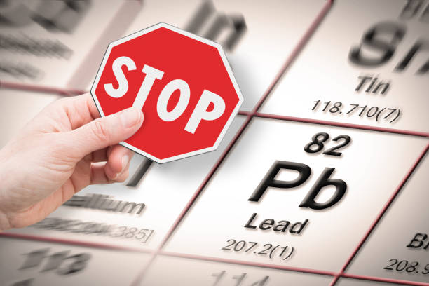 Stop heavy metals - Concept image with hand holding a stop sign against a Lead chemical element with the Mendeleev periodic table on background stock photo