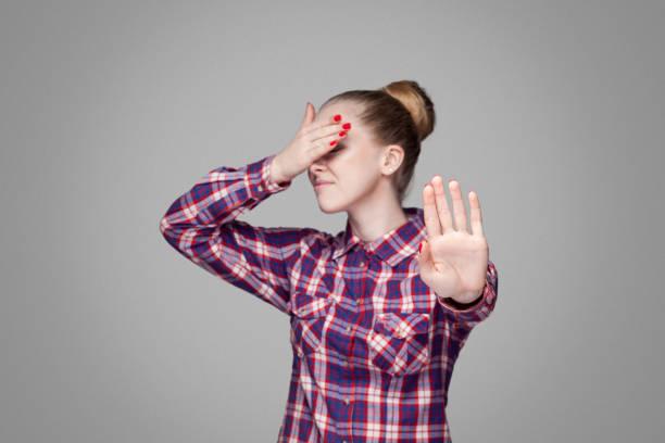 stop, je ne veux pas le voir. belle fille blonde en chemise à carreaux rose, recueillies en chignon coiffure permanent, couvrant les yeux et le blocage avec les mains. - cosmetique store photos et images de collection