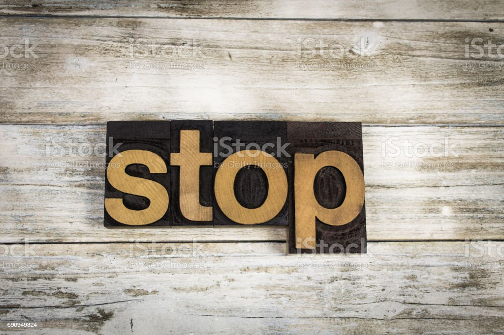 Stop Letterpress Word on Wooden Background stock photo