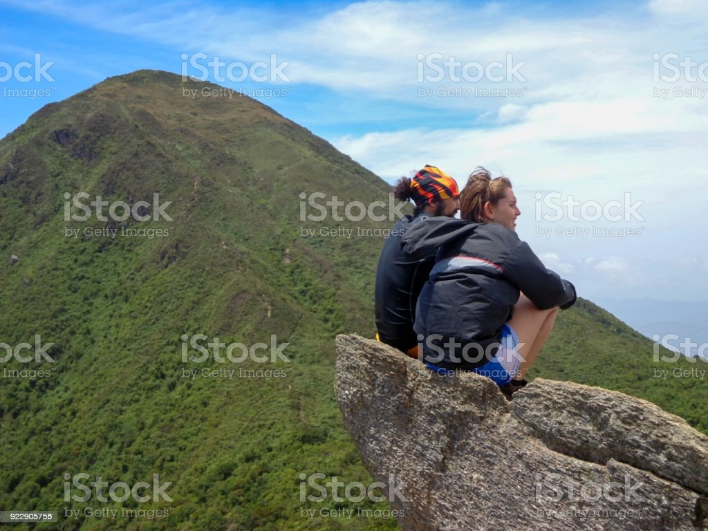 Stop of excurionist, 2 friends Excursionist Sitting on the rock watching the mountain stock photo