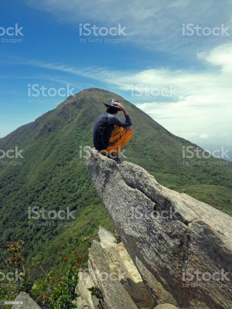 Stop of excurionist, Excursionist Sitting on the rock watching the mountain stock photo