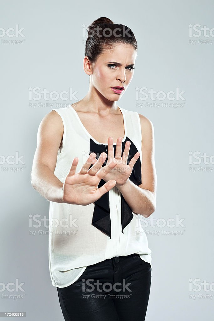 Stop Portrait of irritated young woman with hands out in stop gesture. Studio shot on a grey background. 20-24 Years Stock Photo