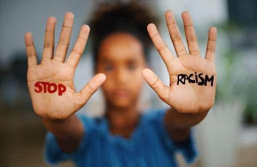 African american girl  standing indoors and looking at the camera. She's showing an message that says Stop Racism on her hands.