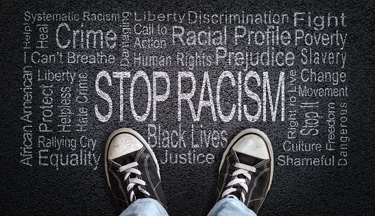 Person standing over Stop Racism word cloud. Concept of stopping discrimination against blacks or people of color because their lives matter.