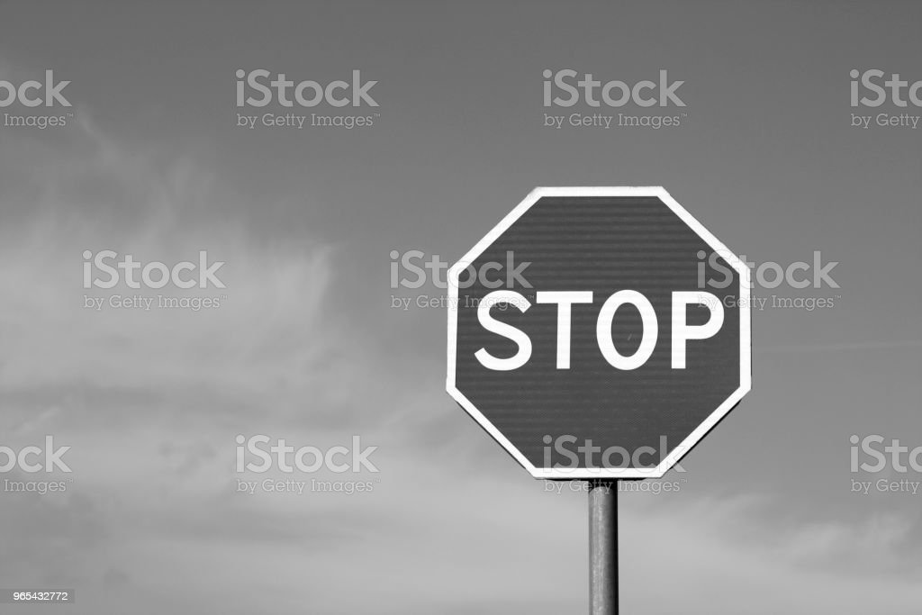 Stop sign against cloudy sky in black and white zbiór zdjęć royalty-free