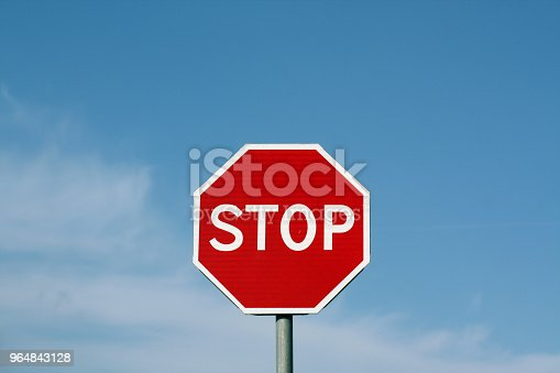 Stop sign against cloudy sky. Abstract background and texture for design.