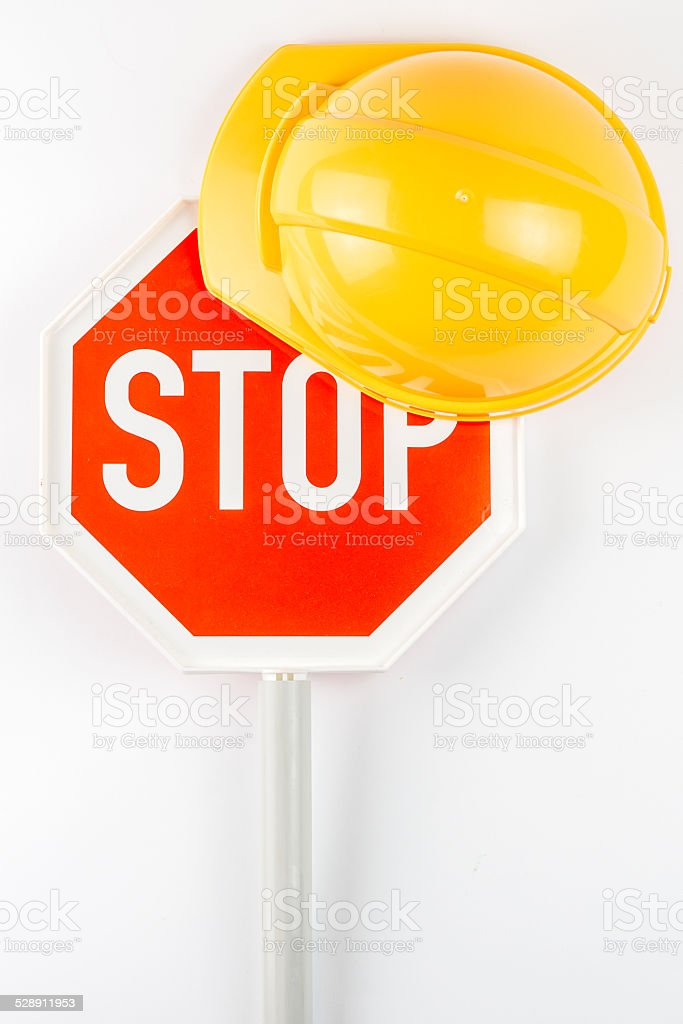 stop sign and orange safety helmet on white background stock photo