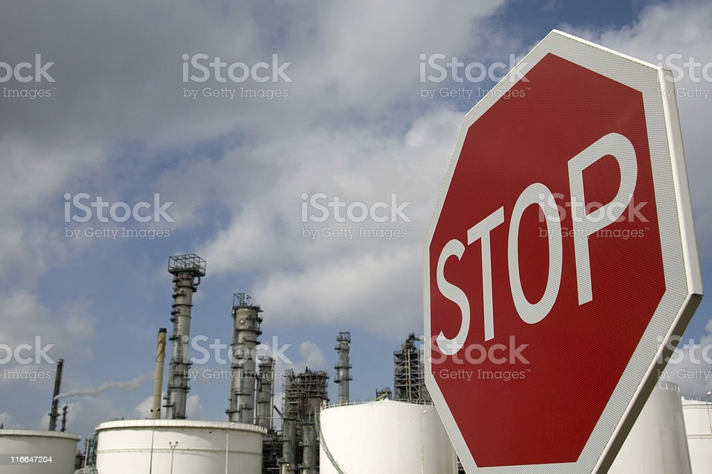 stop sign in front of an oil refinery royalty-free stock photo