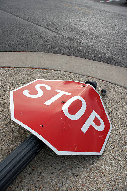 Stop sign lying in the street as the result of an accident stock photo
