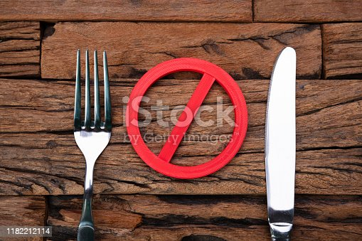 Stop Sign Near Fork And Knife On Wooden Table