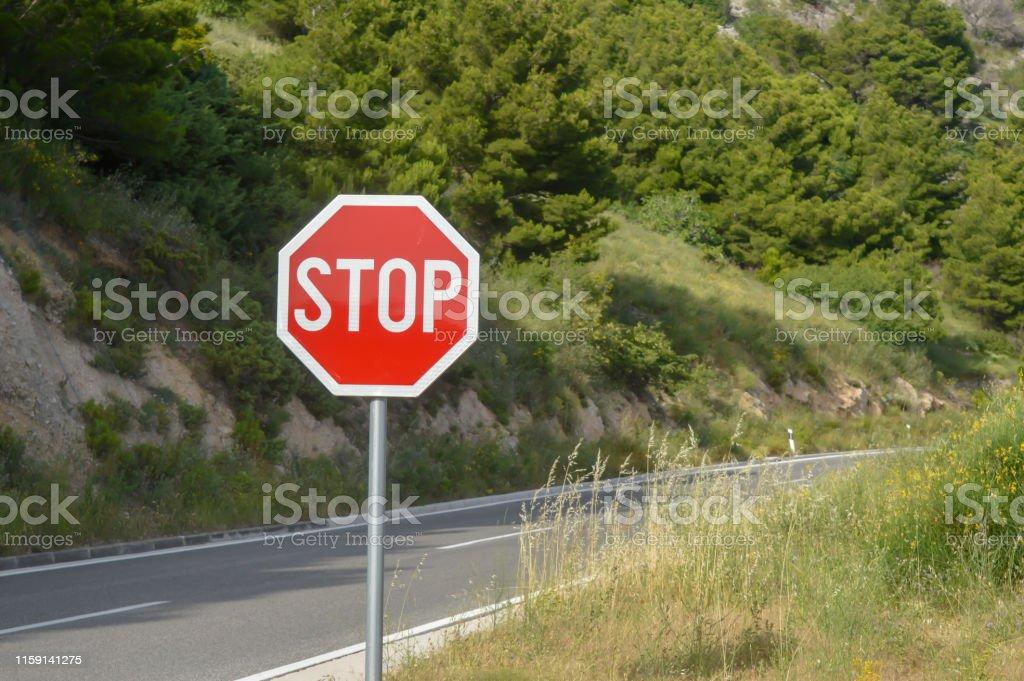 Stop sign on Adriatic Sea coast road. Makarska riviera of Dalmatia,...