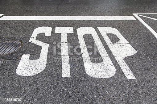 Stop sign on asphalt, detail of a road sign