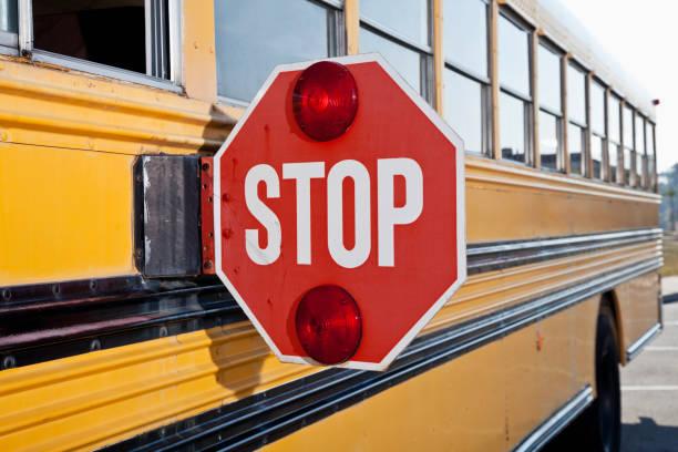 panneau stop sur le côté du bus scolaire - bus scolaires photos et images de collection