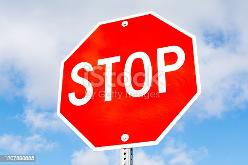 Stop sign with blue skies and clouds in the background.