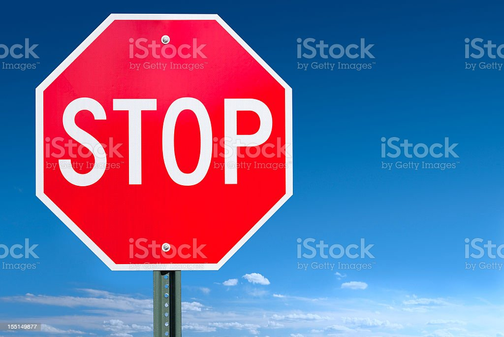 Stop Sign Post Over a Blue Sky Background royalty-free stock photo