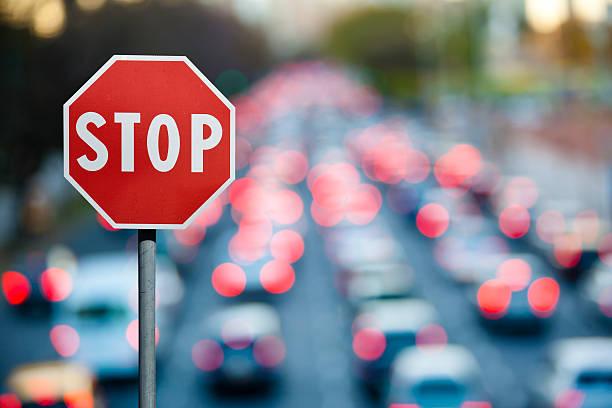 señal de pare al tránsito y coches en la hora pico - stop sign fotografías e imágenes de stock