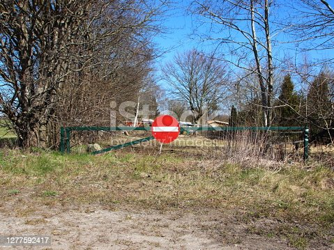 A red and white stop sign on a green barrier at a field entrance.