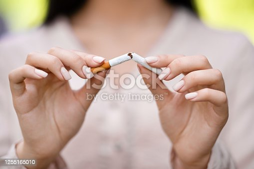Stop smoking concept. Unrecognizable woman breaking cigarette outdoors, closeup image with selective focus
