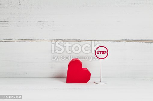 istock Stop Symbol with Read Paper Heart on white wood background. Broken Love Concept with Copy Space. 1204447108