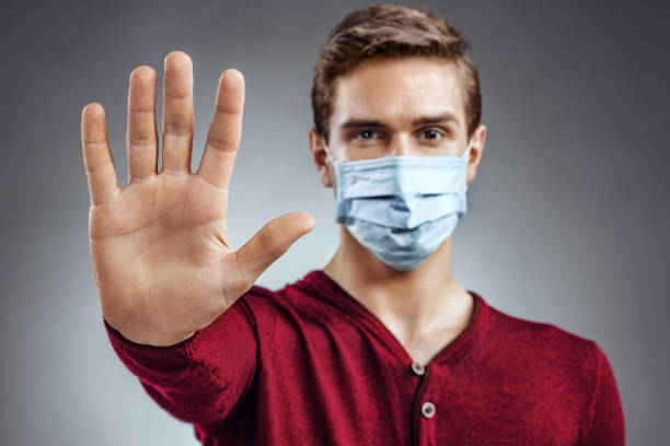 "stop the infection! healthy man showing gesture ""stop"". - polmonite virus foto e immagini stock"