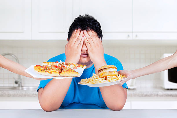 Stop to eat junk food Fat man rejecting to eat junk food. Shoot at home in the kitchen temptation stock pictures, royalty-free photos & images