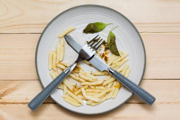 Yiyeceği boşa harcamayı bırak. Artık öğle yemeği ve ahşap bir arka plan üzerinde bir tabak üzerinde çatal. Gıda atıkları kavramı stok fotoğrafı