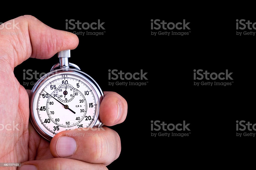 Vintage, analog stopwatch in hand against black background