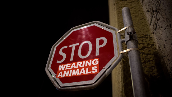 Stop wearing animals red sign on street, wildlife protection campaign message