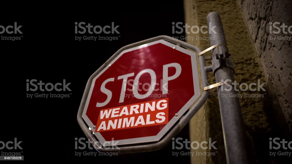 Stop wearing animals red sign on street, wildlife protection campaign message stock photo
