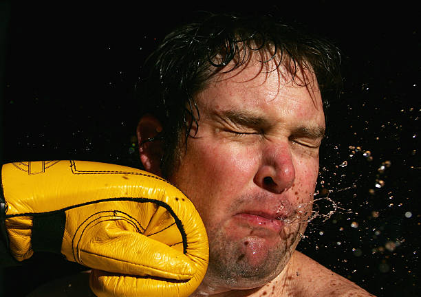 a stop-action photo of a boxing glove striking a man's face - punching stock photos and pictures
