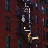 Yellow traffic light in front of a Manhattan apartment and bare trees.